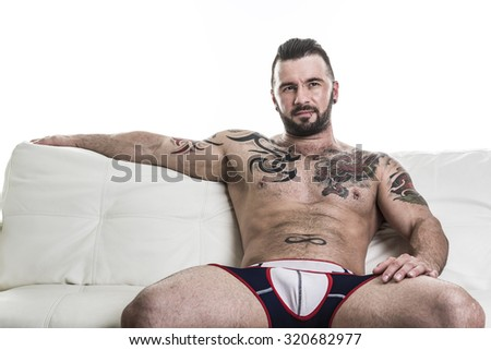 A sexy man with tattoo on the sofa - stock photo