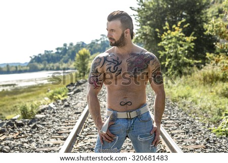 A sexy man with tattoo outside taking good time - stock photo