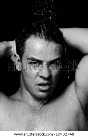A sexy muscular young man in shower washing  himself (black and white) - stock photo