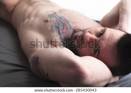 A sexy naked man with tattoo lay in the bed - stock photo
