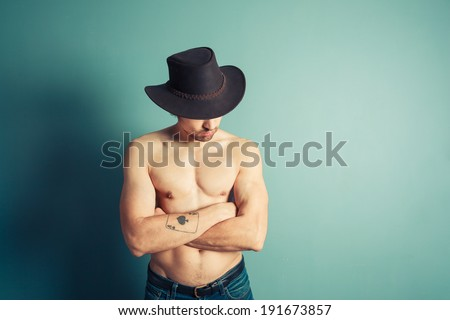 A sexy shirtless cowboy is posing by a blue wall - stock photo