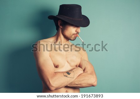 A sexy shirtless young cowboy is smoking a cigarette - stock photo