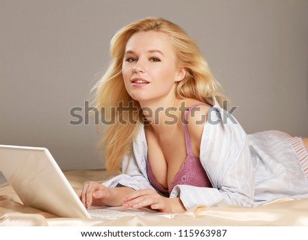A sexy woman lying on the bed with laptop - stock photo