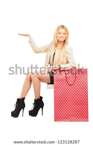A sexy young female gesturing next to a shopping bag isolated on white background - stock photo