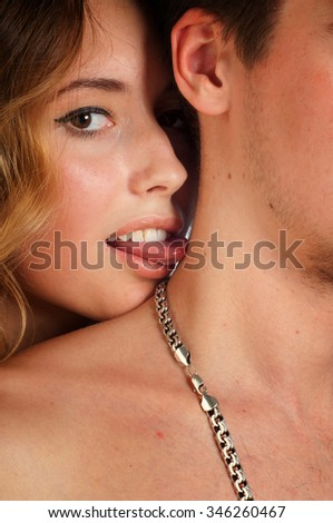 A sexy young topless couple embracing. beautiful young blond woman hugging Man. Young and fit caucasian adult couple in an embrace. Semi-nude and topless against a dark background  - stock photo