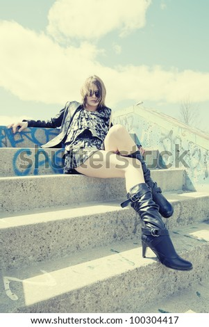 A sexy young woman in mini dress, leather jacket and leather boots sitting on concrete stairs in urban skate park. - stock photo