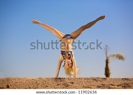A sexy young woman is head first on the tropical beach on a blue (sky) background. - stock photo