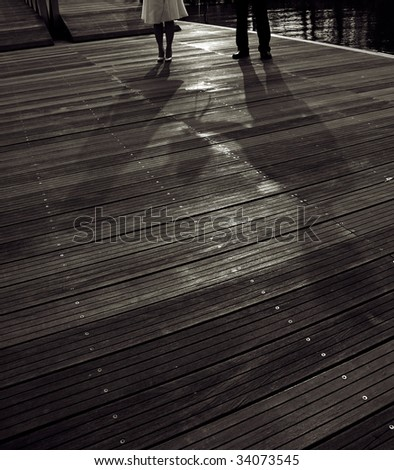 A shadow of lovely couple holding a bouquet of flowers in black and white - stock photo