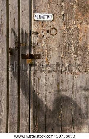 A shadowy figure breaking in to a locked door - stock photo