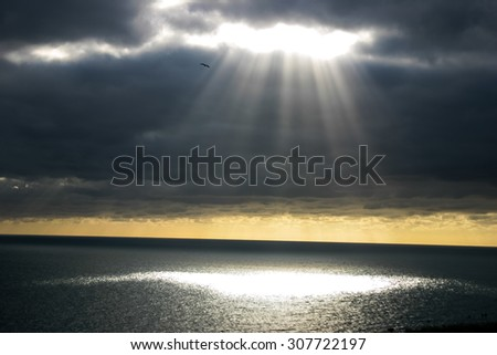 A shaft of light breaking through the dark clouds.  Provides imagery of hope, faith, religion - stock photo