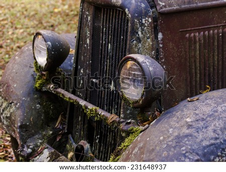 A shallow depth od field photo of the headlight on a run down old truck. - stock photo