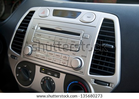 A shallow depth of field close up macro shot of the control panel of a car. Parts shown are the CD player and radio controller, as well as the air conditioning control dials and button. - stock photo