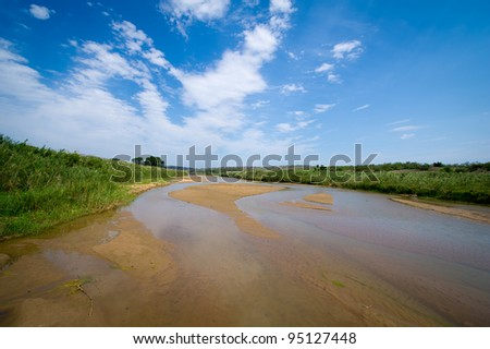A shallow river winds its way through the bush in Hluhluwe/Imfolozi National Park - stock photo