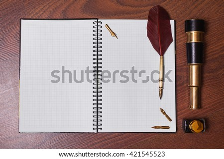 a sheet of paper from a notebook, fountain pen and ink, spyglass on wooden background, copyspace, open notebook, a sheet of paper in the cage  - stock photo