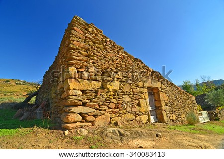 A shepherd's hut in a poor region of northern Portugal. A simple structure made from dry stone walls with no windows and no light - stock photo