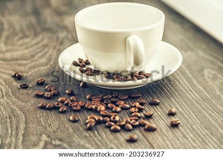 A shiny white cup and coffee beans - stock photo