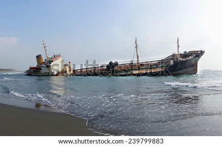 A ship has run aground in shallow waters and is sinking - stock photo