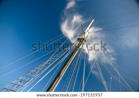 A ship's mast under a cloudy blue sky. - stock photo