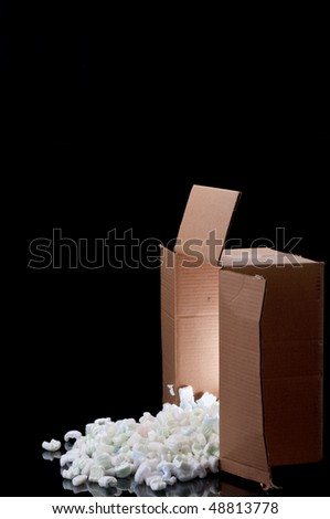 a shipping box with  a glow inside spilling peanuts on a black surface - stock photo