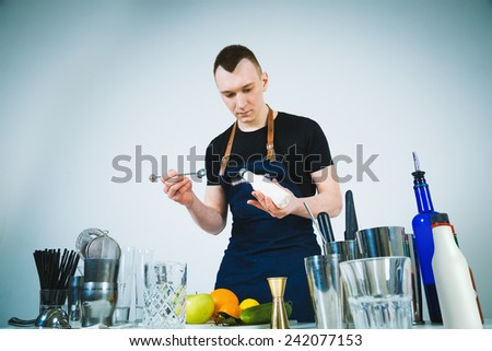 A shoot of young caucasian men in apron as a barmen standing at the table with dishes, preparing a cocktail. - stock photo