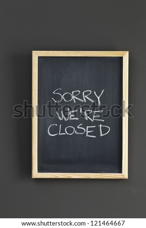"A shop sign says ""Sorry, We're Closed"" sketched on black board - stock photo"