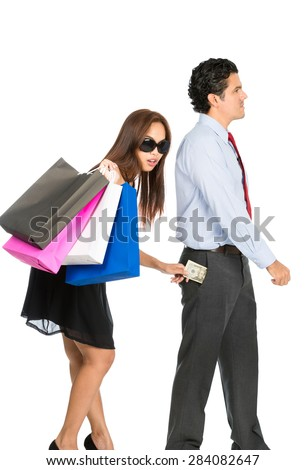 A shopaholic, greedy Asian wife with sunglasses, department store bags, steals money unnoticed from the pants pocket of her husband as he walks away - stock photo