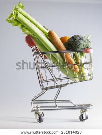 a shopping cart filled with vegetables on a white background - stock photo