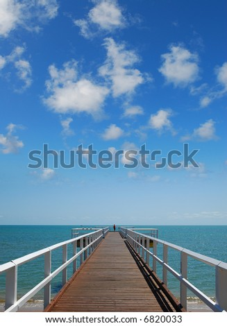 A shore walkway leading the the sea. - stock photo