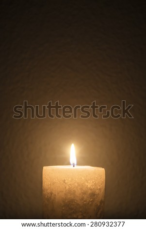 A short candle burns brightly in dark room - portrait interior - stock photo