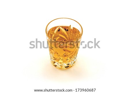 A shot glass of whiskey against a white background - stock photo