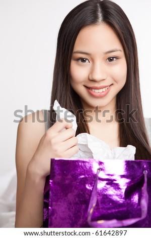 A shot of a beautiful asian girl carrying a shopping bag - stock photo