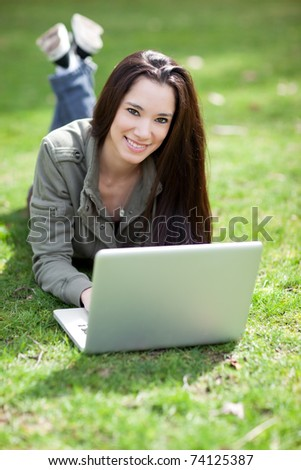 A shot of a beautiful ethnic college student working on her laptop on campus - stock photo