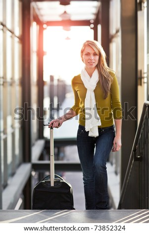 A shot of a beautiful young caucasian woman traveling pulling a luggage - stock photo