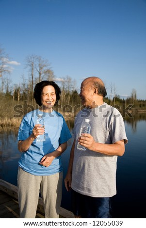 A shot of a happy senior asian couple chatting after a workout - stock photo