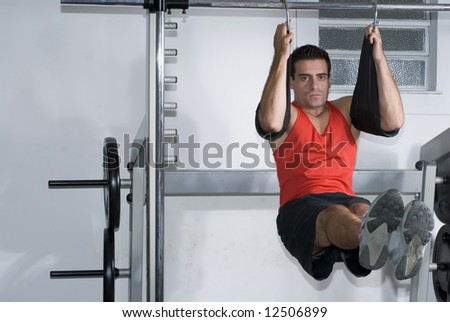 A shot of a man doing hanging crunches. - stock photo