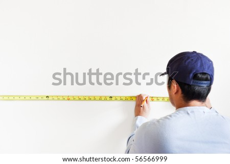 A shot of a man using measurement tape for home improvement - stock photo