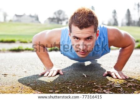 A shot of a mixed race man doing push up outdoor - stock photo