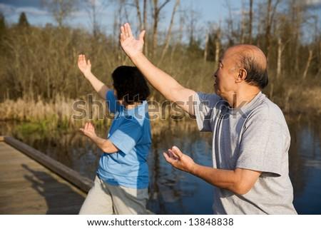 A shot of a senior asian couple doing tai-chi exercise - stock photo