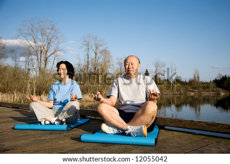 A shot of a senior asian couple practicing yoga and meditating - stock photo