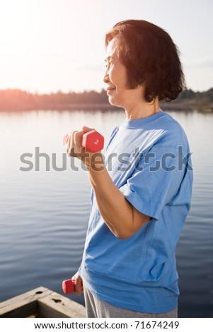 A shot of a senior asian woman exercising and lifting weights - stock photo