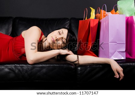A shot of a tired and exhausted beautiful woman sleeping on the couch after shopping - stock photo