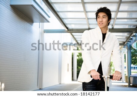 A shot of a young casual asian male riding a scooter - stock photo