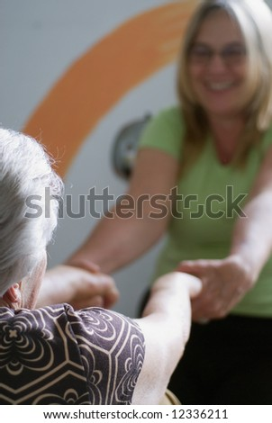 A shot of an adult child help her elderly mother do stretches. - stock photo
