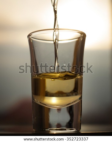A shot of an alcohol beverage being drunk with the snowing background - stock photo
