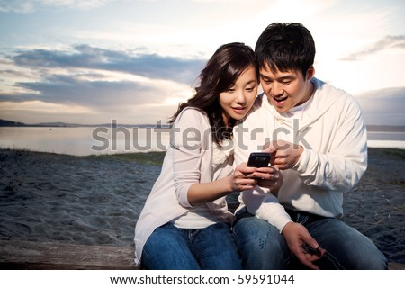 A shot of an asian couple on the phone reading text messages - stock photo