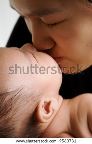A shot of an asian mother kissing her cute baby boy - stock photo