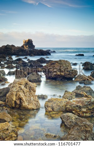 A shot of an early morning Corona Beach in Newport Beach California with the surf crashing into rocks. - stock photo