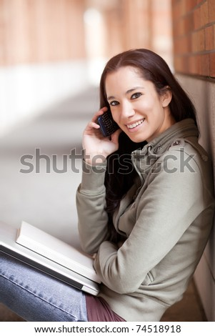 A shot of an ethnic student talking on the phone - stock photo