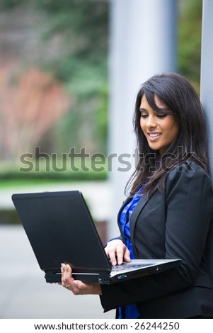 A shot of an indian businesswoman working on her laptop outdoor - stock photo