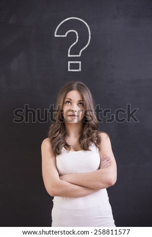 A shot of attractive young woman is standing in front of a blackboard with a question sign. - stock photo